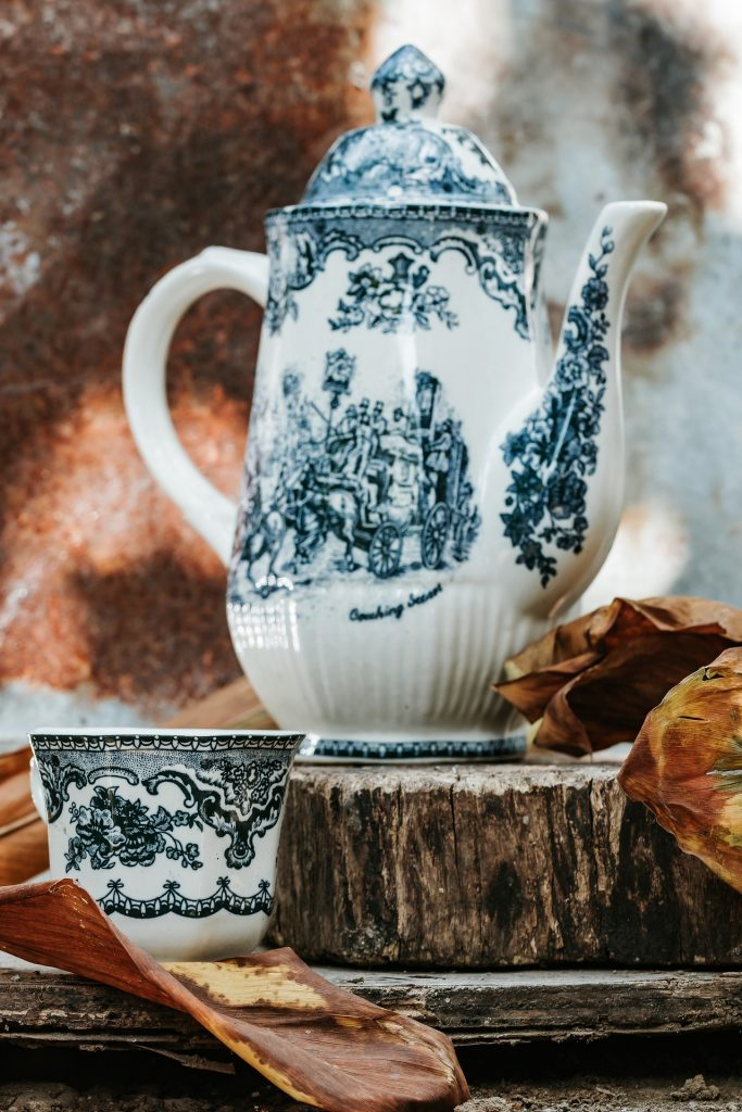 a tall teapot white base with navy blue flora print with matching tea cup. Sitting on a wooden block.