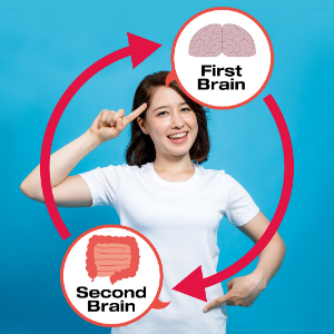 women pointing to head, first brain, and pointing to stomach, second brain