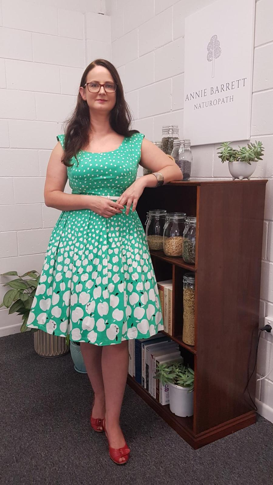 Naturopath Caloundra Sunshine Coast Annie Barrett wearing a green and white dress and red shoes, leaning against a bookshelf filled with different herbal teas and books
