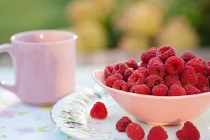 a bowl of raspberries to use to make banana raspberry muffins