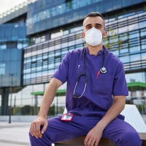 photo of a shift worker sitting outside of a hospital
