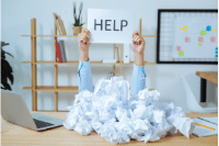 man at work buried under a pile of paperwork holding up a help sign
